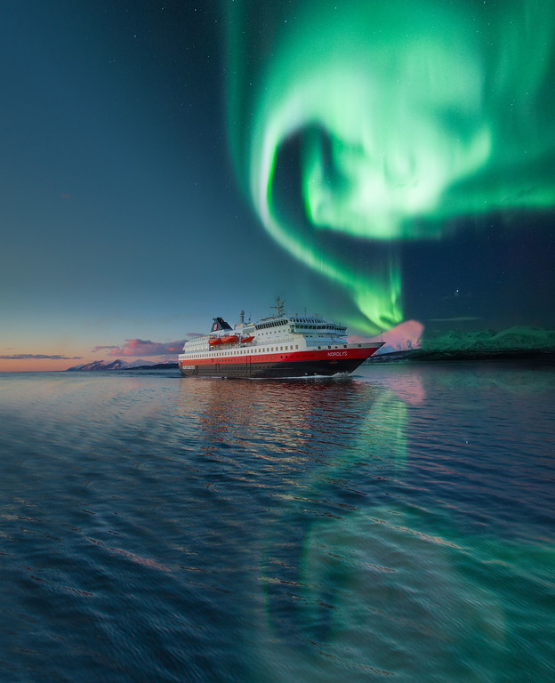 Green lights swirl in the sky near a ship.