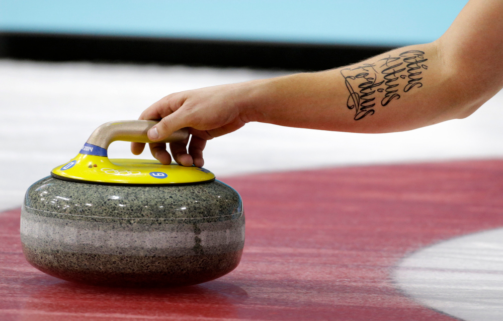 """. Swedenís Fredrik Lindberg delivers the rock during the men\'s curling bronze medal game against China at the 2014 Winter Olympics, Friday, Feb. 21, 2014, in Sochi, Russia. His tattoo is Latin for \""""Faster, Higher, Stronger,\"""" the Olypmic motto. (AP Photo/Robert F. Bukaty)"""