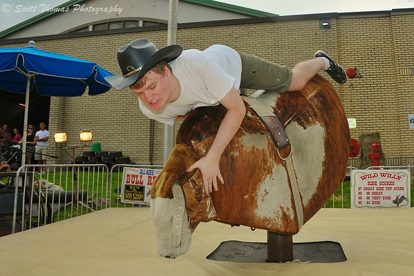 A man about to be dumped off of Wild Willy, a mechanical bull, at The Great New York State Fair in Syracuse, New York on Saturday, August 23, 2014.