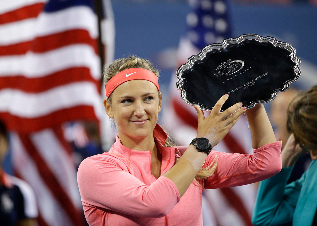 . Victoria Azarenka, of Belarus, holds up the second place trophy after losing to Serena Williams during the women\'s singles final of the 2013 U.S. Open tennis tournament, Sunday, Sept. 8, 2013, in New York. (AP Photo/David Goldman)