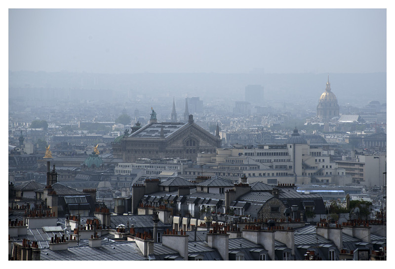 View of Paris through the haze - from Sacre Coeur. The structure in the center is one of the train stations.