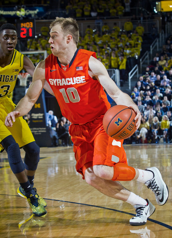 . Michigan guard Caris LeVert, left, defends Syracuse guard Trevor Cooney (10) in the first half of an NCAA college basketball game at Crisler Center in Ann Arbor, Mich., Tuesday, Dec. 2, 2014. (AP Photo/Tony Ding)