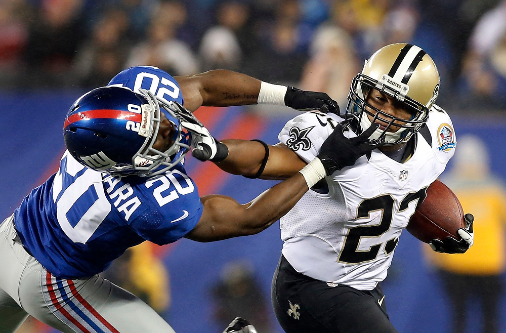 . New Orleans Saints running back Pierre Thomas (R) collides with New York Giants\' defender Prince Amukamara in the third quarter of their NFL football game in East Rutherford, New Jersey, December 9, 2012. REUTERS/Mike Segar