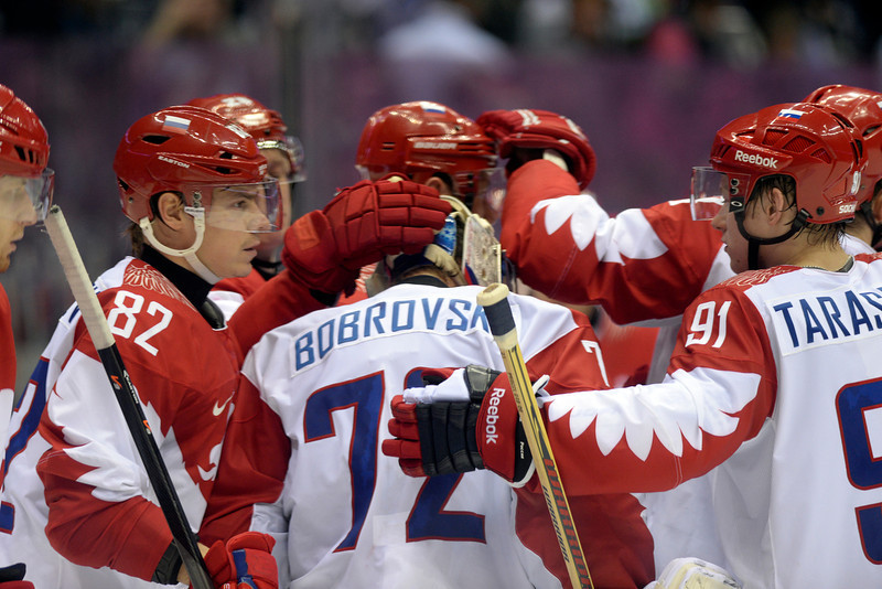 . Teammates console Sergei Bobrovski (72) of the Russia after he gave up the game-winning shot to T.J. Oshiet (74) of the U.S.A. during  the U.S.A.\'s shootout-win at Bolshoy arena. Sochi 2014 Winter Olympics on Saturday, February 15, 2014. (Photo by AAron Ontiveroz/The Denver Post)