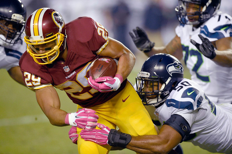 . Washington Redskins running back Roy Helu (29) is hauled o the turf by Seattle Seahawks outside linebacker K.J. Wright (50) during the first half of an NFL football game in Landover, Md., Monday, Oct. 6, 2014. (AP Photo/Nick Wass)