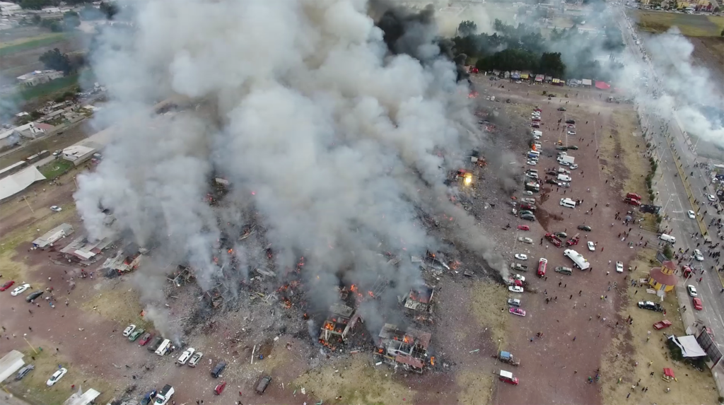 . This image made from video provided by APTN, shows a view from a drone of smoke billowing from the San Pablito Market, where an explosion ripped through a fireworks market in Tultepec, Mexico, Tuesday, Dec. 20, 2016. Sirens wailed and a heavy scent of gunpowder lingered in the air after the afternoon blast at the market, where most of the fireworks stalls were completely leveled. According to the Mexico state prosecutor there are at least 26 dead. (Pro Tultepec via APTN)