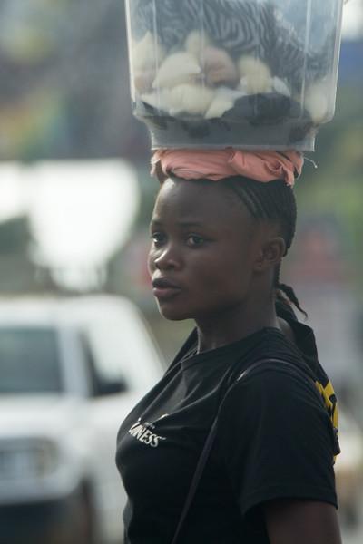 Monrovia, Liberia October 13, 2017 - A woman walks through traffic in Monrovia.