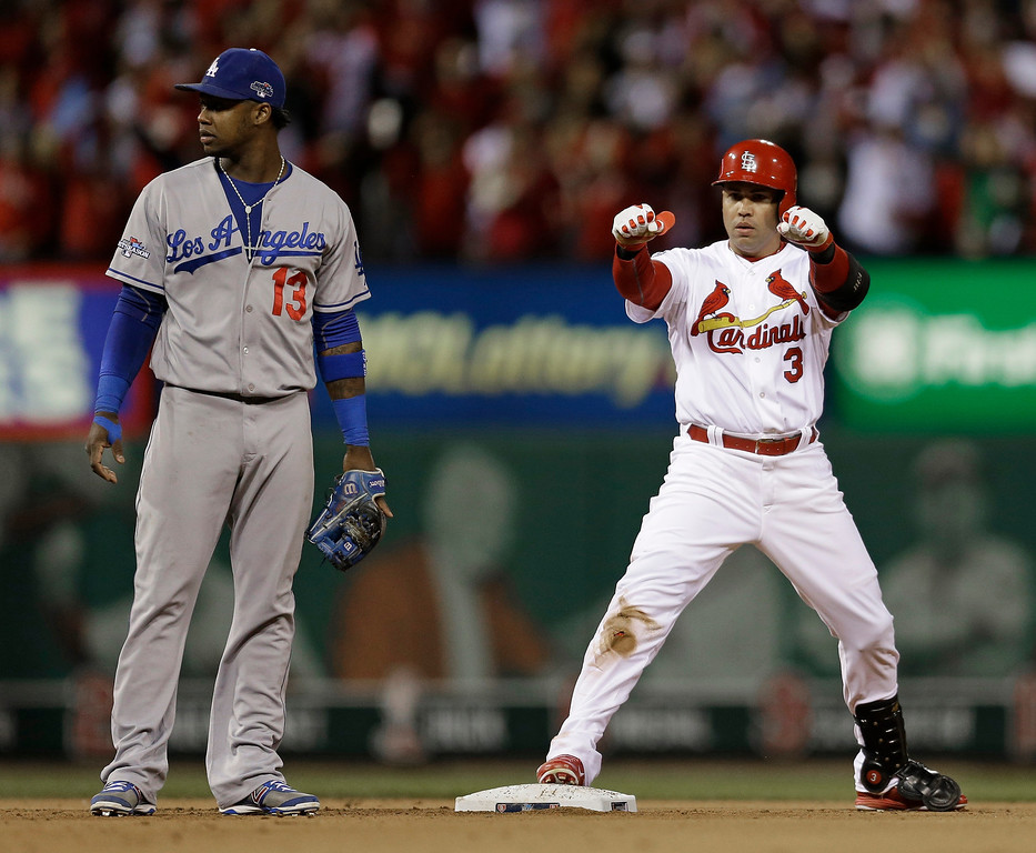 . St. Louis Cardinals\' Carlos Beltran reacts after his run-scoring hit during the third inning of Game 6 of the National League baseball championship series against the Los Angeles Dodgers, Friday, Oct. 18, 2013, in St. Louis. Los Angeles Dodgers shortstop Hanley Ramirez (13) looks on. (AP Photo/Jeff Roberson)