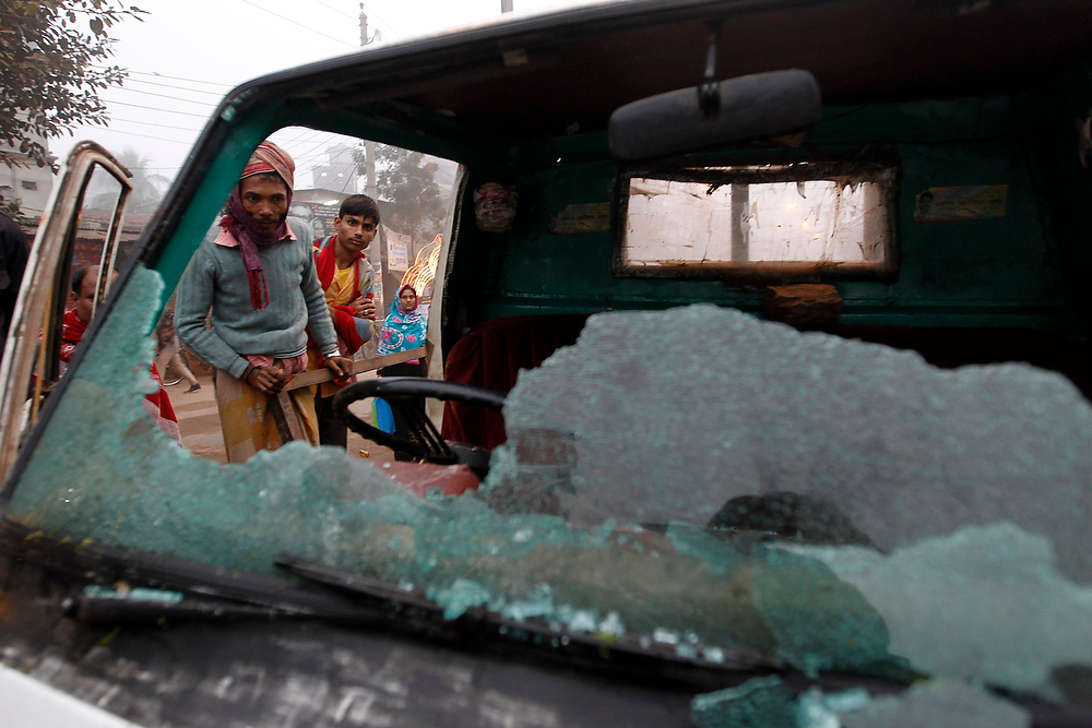Description of . People look at a truck after activists of different radical Islamist parties vandalized it during a strike in Dhaka on December 20, 2012. Four of 12 radical like-minded Islamist parties have called for a nationwide dawn to dusk strike on Thursday, to protest against the efforts of the left parties to seek a ban on
