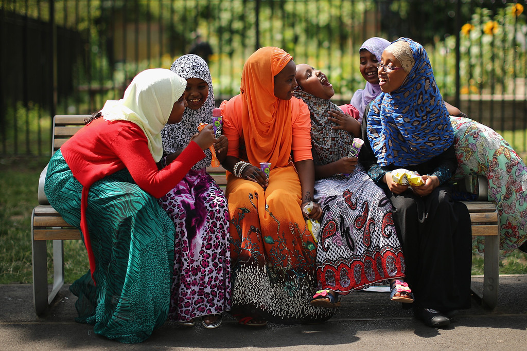 . LONDON, ENGLAND - AUGUST 08:  Girls eat iced lollies on a bench in Burgess Park on August 8, 2013 in London, England. The Muslim holiday Eid marks the end of 30 days of dawn-to-sunset fasting during the holy month of Ramadan. (Photo by Dan Kitwood/Getty Images)