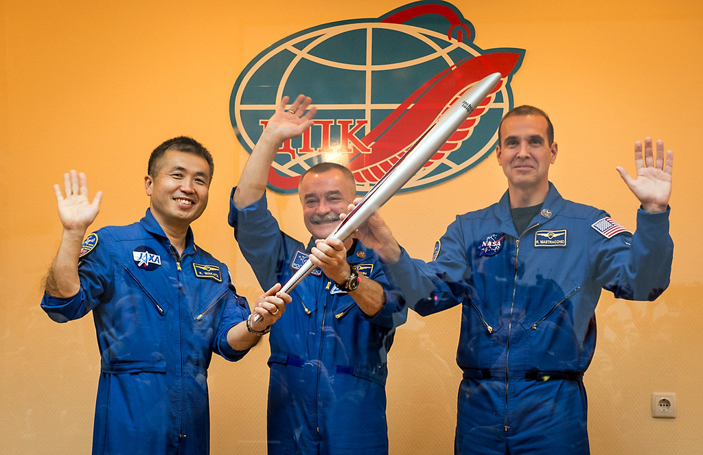 . This NASA handout photo shows (from L) Expedition 38 Soyuz Flight Engineer Koichi Wakata of the Japan Aerospace Exploration Agency, Commander Mikhail Tyurin of Roscosmos and Flight Engineer Rick Mastracchio of NASA, waving farewell as they hold the Olympic torch prior to boarding the Soyuz TMA-11M rocket for launch, November 7, 2013 at the Baikonur Cosmodrome in Kazakhstan.  The Olympic torch have a four-day visit to the International Space Station.  Tyurin, Mastracchio, and, Wakata will spend the next six months aboard the International Space Station.  AFP PHOTO / NASA / BILL INGALLS /AFP/Getty Images