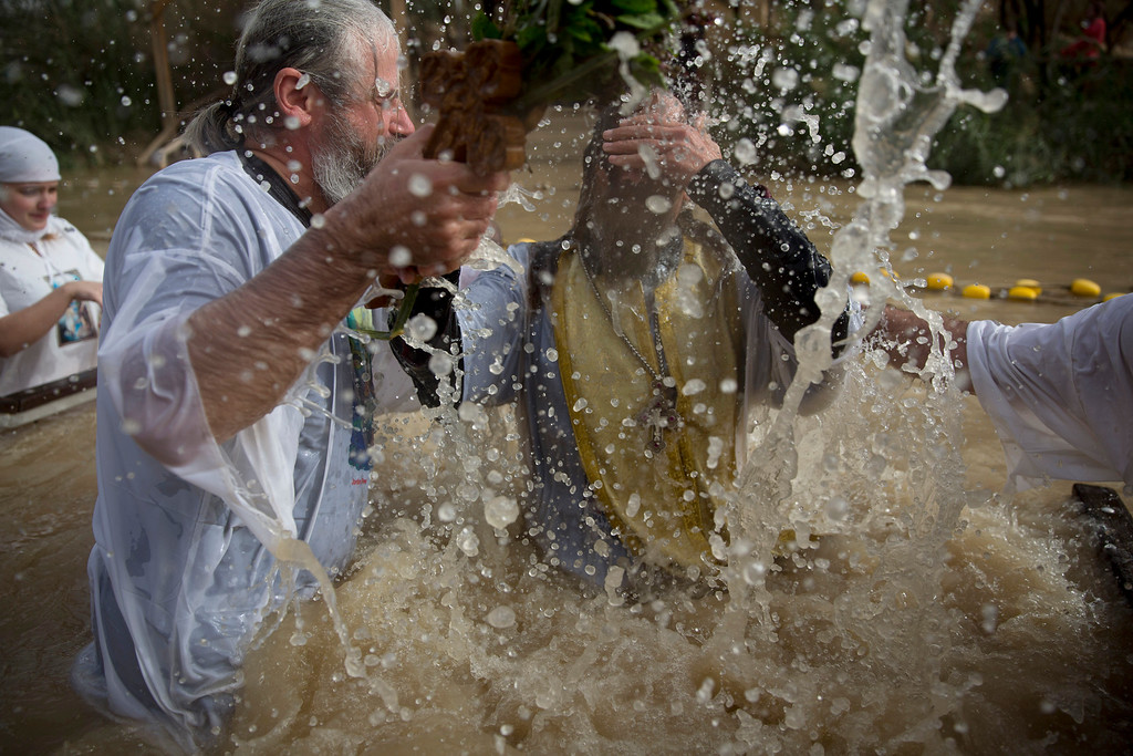 . A Christian Orthodox priest re-enacts the baptism of Jesus, during the traditional Epiphany baptism ceremony at the Qasr-el Yahud baptism site in the Jordan river near the West Bank town of Jericho, Monday, Jan. 18, 2016. The site is traditionally believed by many to be the place where Jesus was baptized. (AP Photo/Ariel Schalit)