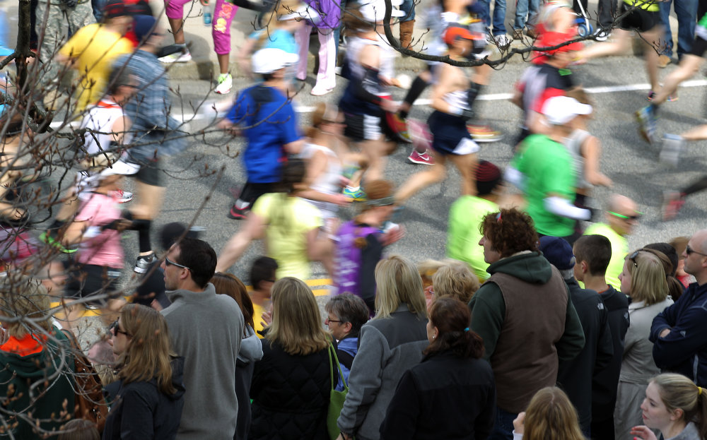 . Spectators watch runners pass by at the start of the 117th running of the Boston Marathon, in Hopkinton, Mass., Monday, April 15, 2013. (AP Photo/Stew Milne)