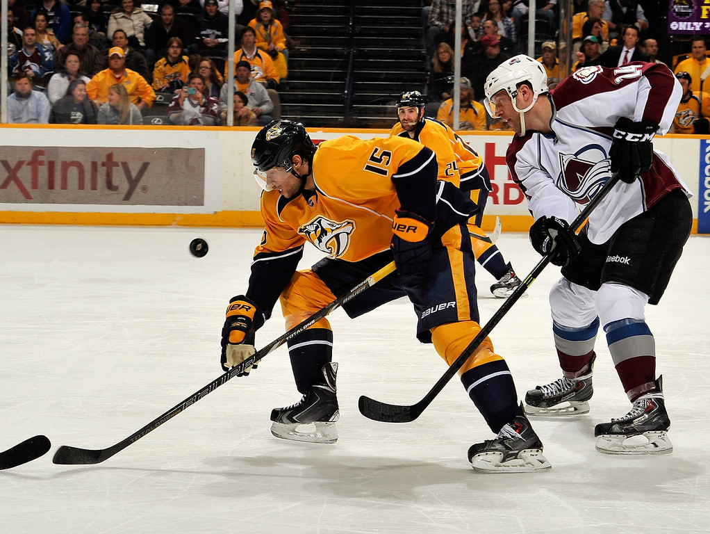 . Craig Smith #15 of the Nashville Predators and Marc-Andre Cliche #24 of the Colorado Avalanche chase a bouncing puck at Bridgestone Arena on March 25, 2014 in Nashville, Tennessee.  (Photo by Frederick Breedon/Getty Images)