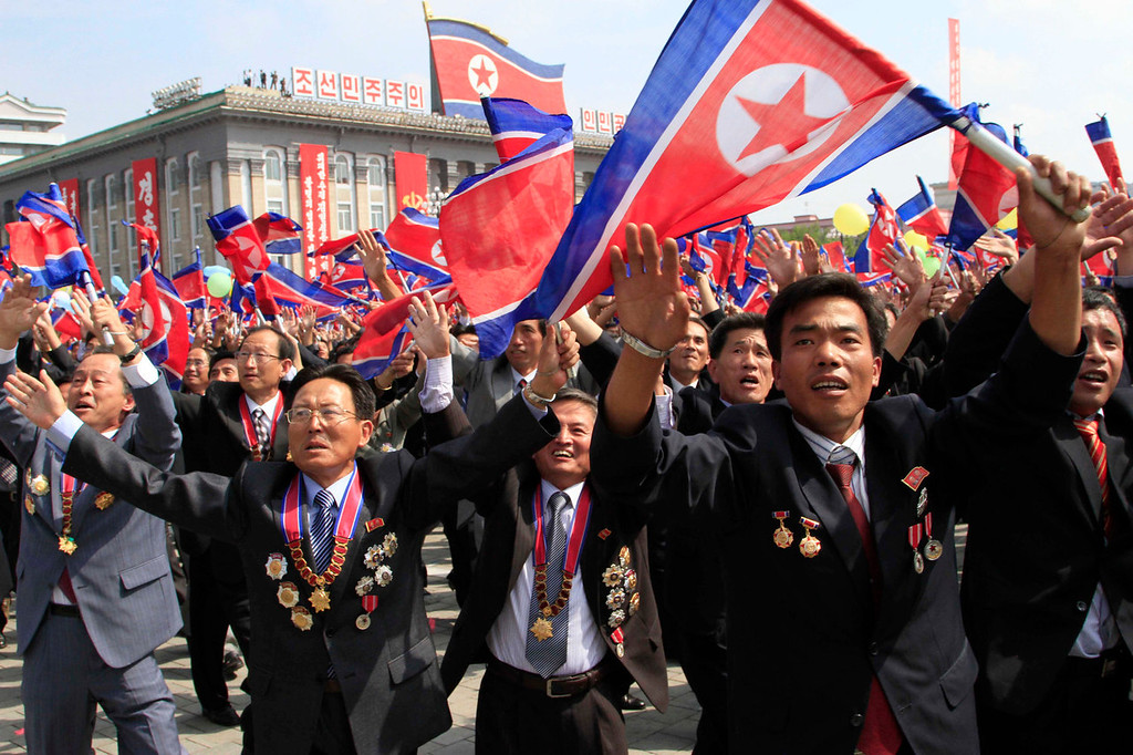 . North Korean scientists wave their national flag during a military parade at Kim Il Sung Square to mark the 65th anniversary of the country\'s founding in Pyongyang, North Korea, Monday, Sept. 9, 2013. (AP Photo/Jon Chol Jin)