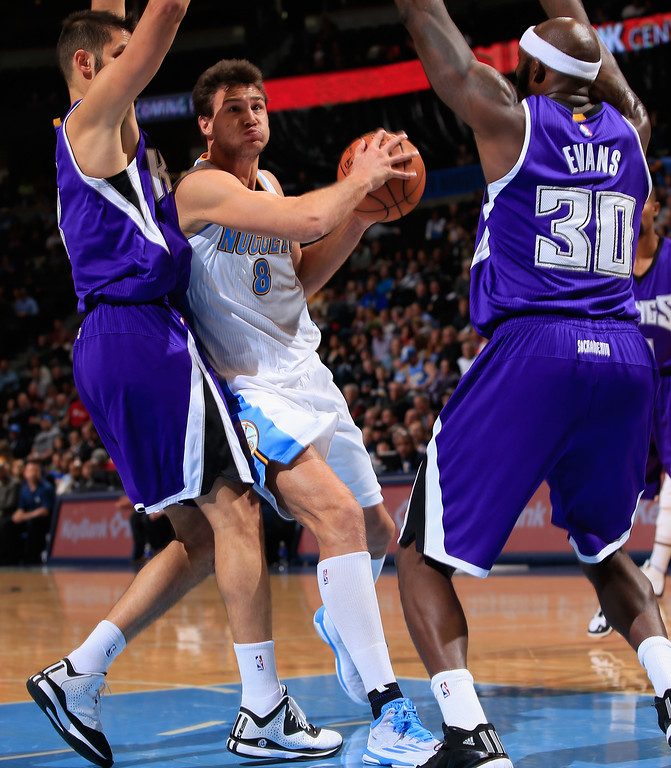 . DENVER, CO - NOVEMBER 03:  Danilo Gallinari #8 of the Denver Nuggets drives to the basket against Omri Casspi #18 and Reggie Evans #30 of the Sacramento Kings at Pepsi Center on November 3, 2014 in Denver, Colorado. The Kings defeated the Nuggets 110-105. NOTE TO USER: User expressly acknowledges and agrees that, by downloading and or using this photograph, User is consenting to the terms and conditions of the Getty Images License Agreement.  (Photo by Doug Pensinger/Getty Images)