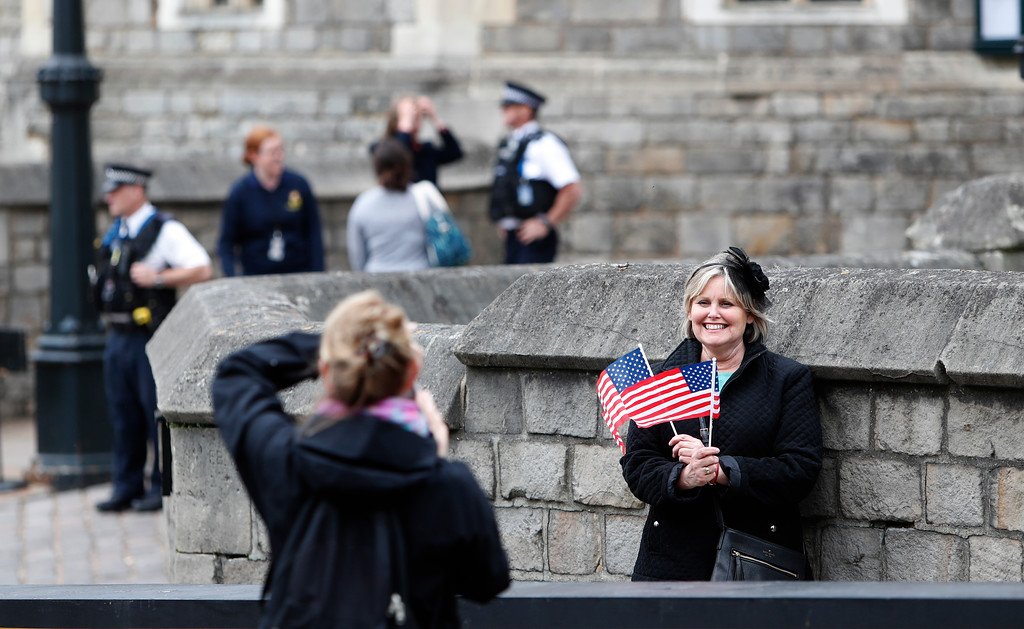 . Diane Calderon of Long Island, in the US, poses for a photograph holding two United States flags outside Windsor Castle, during a visit to Windsor, England, Wednesday, May 16, 2018. Preparations continue in Windsor ahead of the royal wedding of Britain\'s Prince Harry and Meghan Markle Saturday May 19. (AP Photo/Alastair Grant)