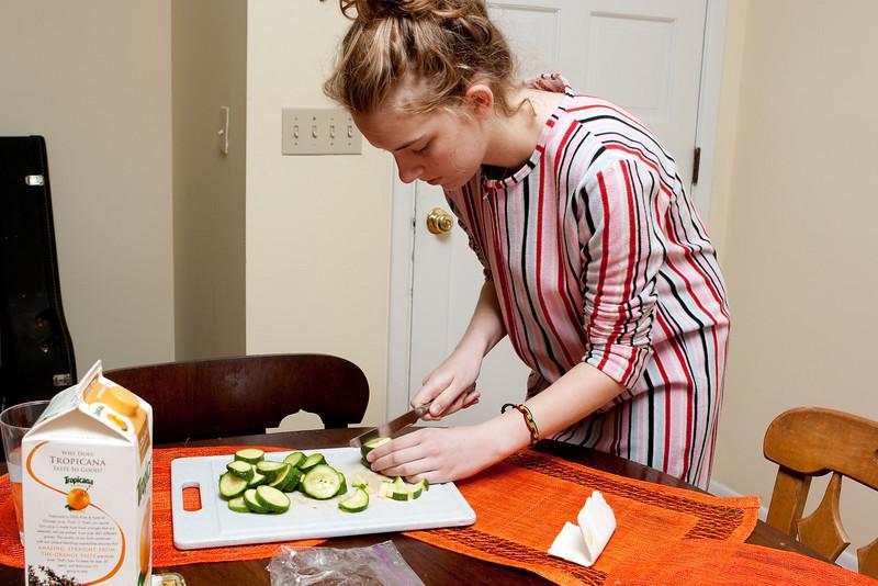 Claudia chops zucchini.