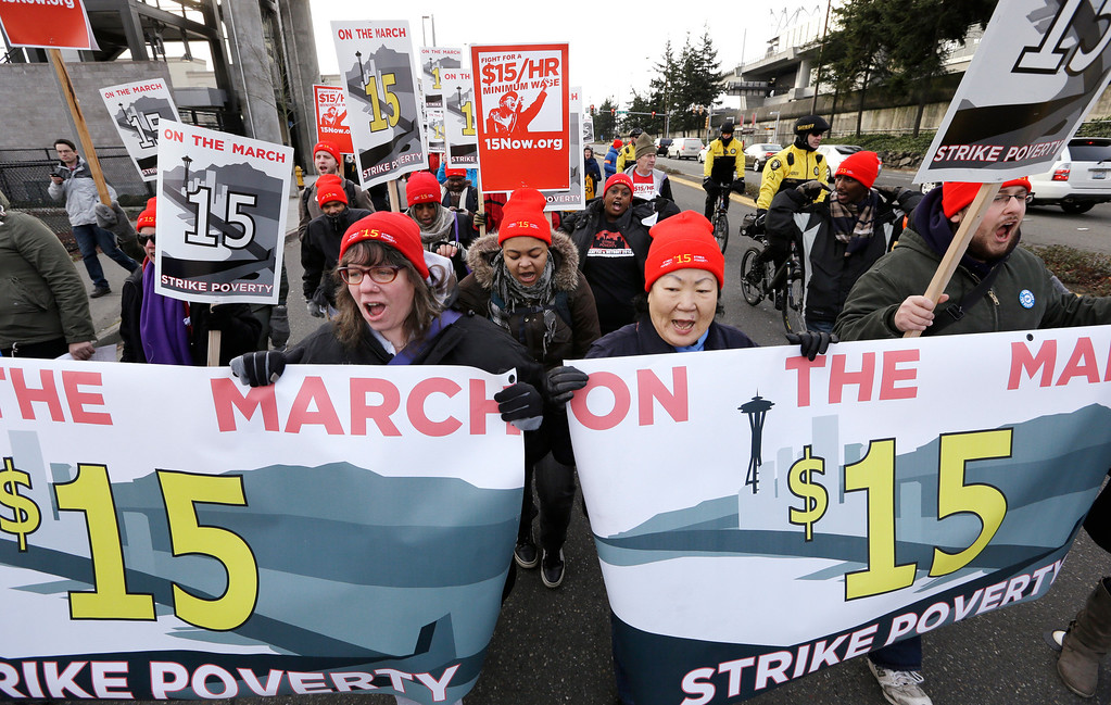 . Protesters begin a day-long march in support of fast-food workers Thursday, Dec. 5, 2013, in SeaTac, Wash. (AP Photo/Elaine Thompson)