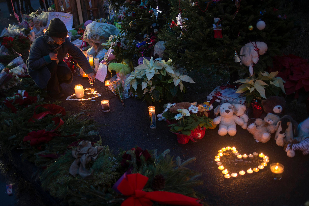 . A woman lights candles at a memorial for victims of the Sandy Hook Elementary shooting near the school in Sandy Hook Village in Newtown, Connecticut December 16, 2012. Worshippers filled Sunday services to mourn the victims of a gunman\'s elementary school rampage that killed 20 children and six adults with the president due to appear later at an interfaith vigil to help this shattered Connecticut town recover.  REUTERS/Adrees Latif