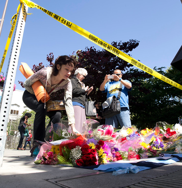 . Mourners pause and lay flowers at the scene on Kittredge Street where a balcony collapsed, sending 13 people plunging to the street below, Tuesday, June 16, 2015, in Berkeley, Calif. Six people were killed, and seven more were transported to area hospitals. (D. Ross Cameron/Bay Area News Group)