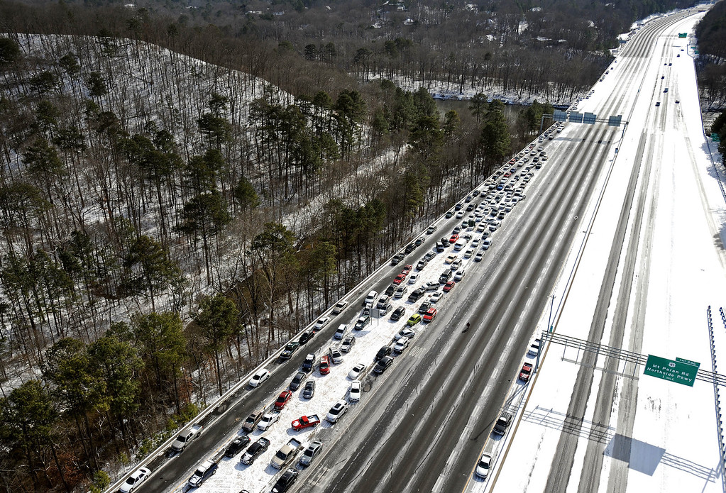 . In this view looking south toward downtown Atlanta near the I-75 Chattahoochee River overpass, abandoned cars are piled up on the median of the ice-covered interstate after a winter snow storm slammed the city with over 2 inches of snow that turned highways into parking lots creating massive traffic jams lasting through Wednesday, Jan. 29, 2014, in Atlanta. While such amounts of accumulation barely quality as a storm in the north, it was enough to paralyze the Deep South. (AP Photo/David Tulis)