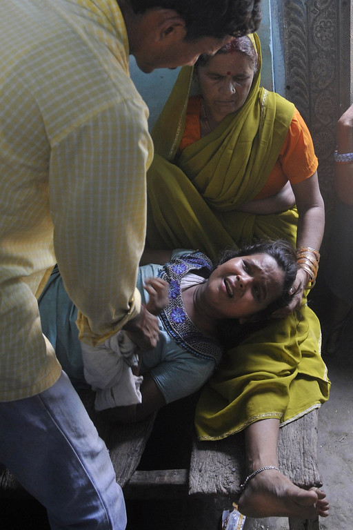 . A grief-stricken mother (C), whose son died after consuming a free mid day meal at a school in India\'s Bihar state, is consoled at Gandaman in Saran District on July 17, 2013.  Twenty-two children have died after eating a free lunch feared to contain poisonous chemicals at an Indian primary school, officials said, as the tragedy sparked angry street protests.  AFP PHOTOSTR/AFP/Getty Images