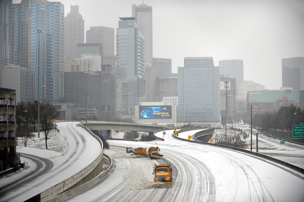 """. Snow plows clear Interstate 75/85 on the downtown connector while transportation and business grinds to a halt during a winter storm on Wednesday, Feb. 12, 2014, in Atlanta.  Across the South, winter-weary residents woke up Wednesday to a region encased in ice, snow and freezing rain, with forecasters warning that the worst of the potentially \""""catastrophic\"""" storm is yet to come. (AP Photo/David Tulis)"""