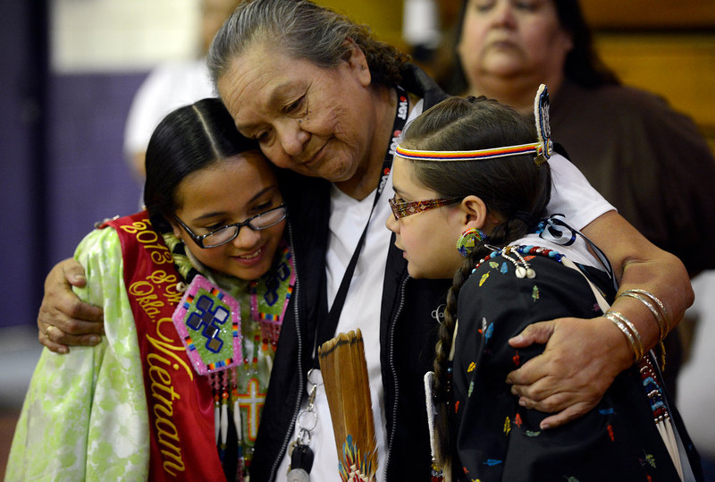 """. Patricia Bointy, center, hugs her \""""adopted\"""" granddaughter, Samantha Wells, 11, and Samantha\'s good friend, Ramysee Kiley Davenport, 10, right, during the 22nd annual Sand Creek Descendants Gathering in Anadarko Oklahoma Saturday, December 1st, 2012. Bointy\'s sister Linda Tsonetokoy, passed away the day before the gathering. Nearly 100 descendants of the Sand Creek Massacre gathered at the Anadarko High School gym for traditional Gourd dancing, food and other activities and also to get updates on legal action towards the U.S. for the massacre which left over 150 Cheyenne and Arapaho Indians dead in southeast Colorado November 29th, 1864. The Denver Post/ Andy Cross"""