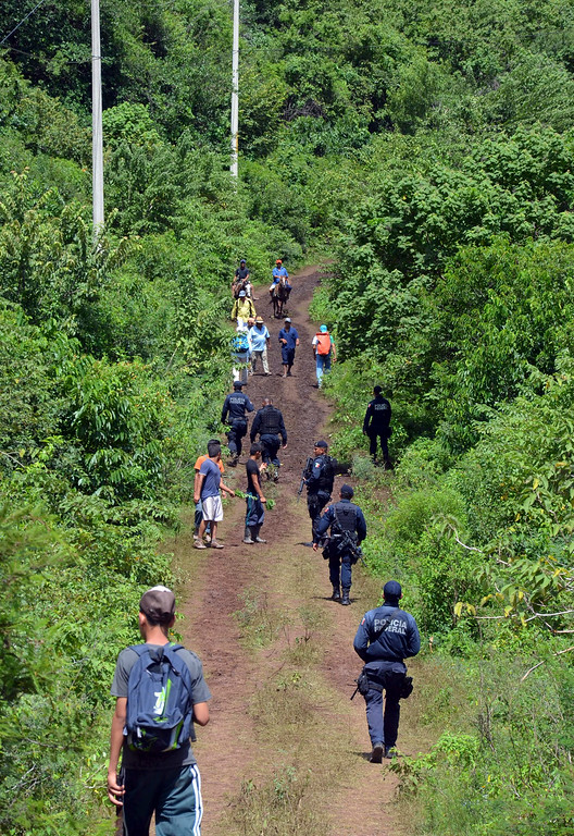 . Federal police patrol a small country road after a slew of robbery reports of residents affected by Tropical Storm Manuel, who were trekking supplies back to their homes, near Tepechicotlan, Mexico, Thursday, Sept. 19, 2013. (AP Photo/Alejandrino Gonzalez)