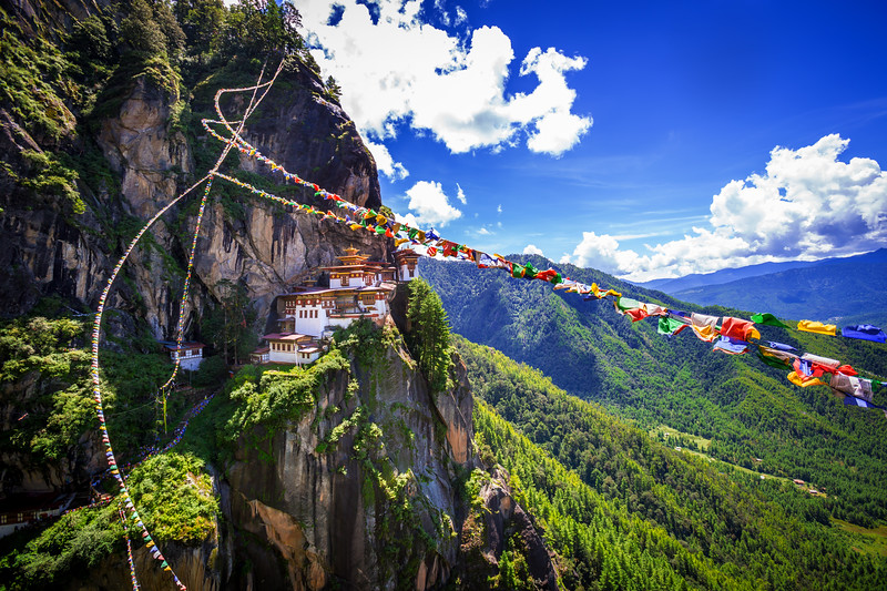Colorful prayer flags are strung along a cliff at Tiger's Nest.