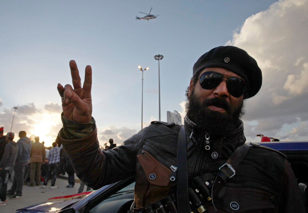 Description of . A Libyan rebel gives the victory sign during a celebration to commemorate the second anniversary of the revolution that ousted Moammar Gadhafi, in Benghazi, Libya, Friday, Feb, 15, 2013. (AP Photo/Mohammad Hannon)