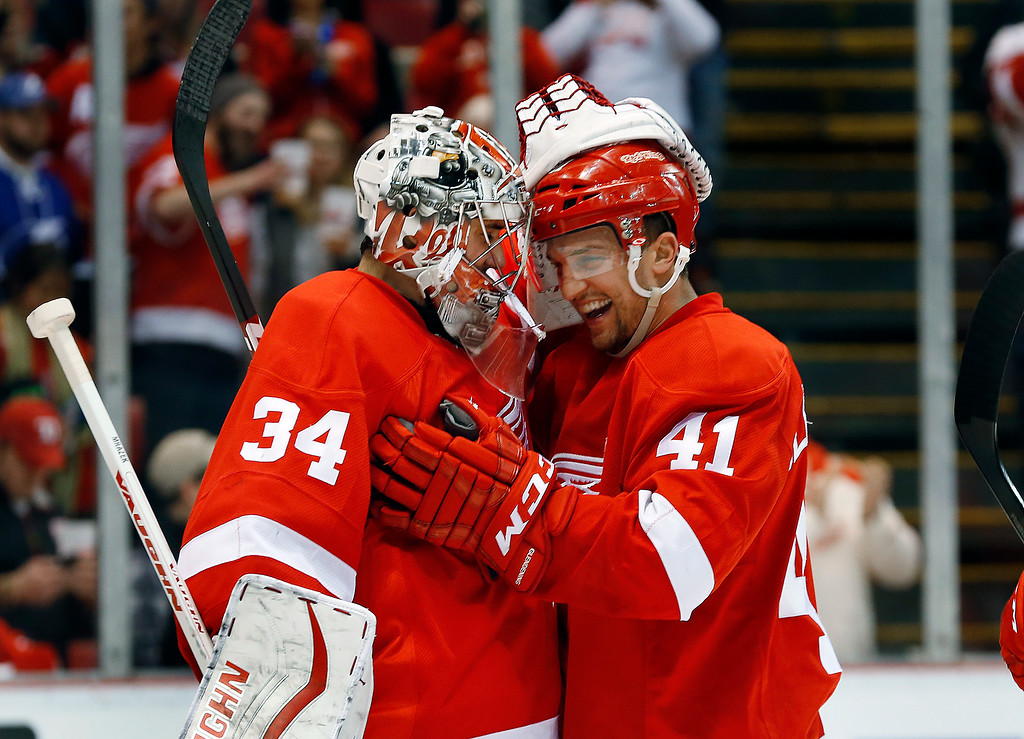 . Detroit Red Wings goalie Petr Mrazek (34) celebrates with Luke Glendening (41) after they shutout the Tampa Bay Lightning 4-0 in an NHL hockey game in Detroit, Saturday, March 28, 2015. Detroit won 4-0. (AP Photo/Paul Sancya)