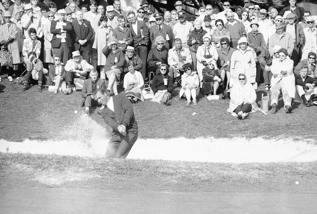 . Arnold Palmer, left, blasts from the trap on the third in the final round of the Crosby National Pro-Am, Jan. 23, 1967, Pebble Beach, Calif. Palmer, tied with Jack Nicklaus, and one stroke behind leader Billy Casper going into today\'s round, bogied the par four hole. (AP Photo)
