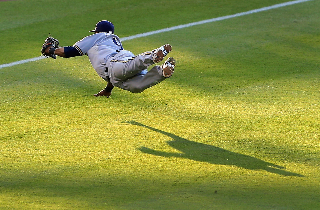 . DENVER, CO - JULY 26:  Shortstop Jean Segura #9 of the Milwaukee Brewers makes a diving catch on a pop fly by Charlie Blackmon #19 of the Colorado Rockies in the second inning at Coors Field on July 26, 2013 in Denver, Colorado.  (Photo by Doug Pensinger/Getty Images)