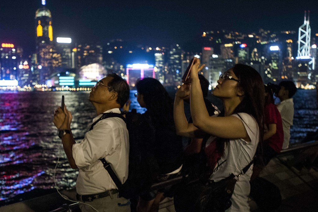 . People take photographs of a lunar eclipse from The Avenue of Stars in Hong Kong on October 8, 2014.   The total lunar eclipse is the second of two in 2014 and the second in a tetrad (four total lunar eclipses in series).  AFP PHOTO / XAUME  OLLEROS/AFP/Getty Images