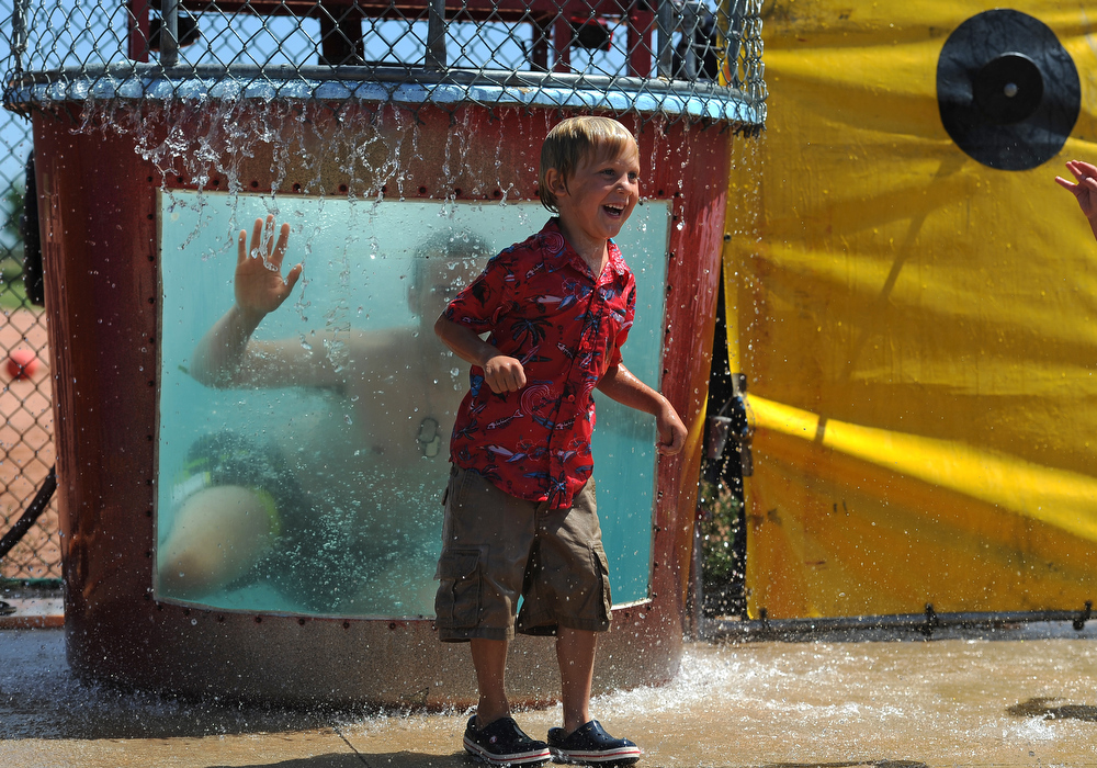 . Miles Southard, 4, screams with delight as he gets covered in water as he watches A1C Andrew McCormick of the 140th Maintenance Wing get dunked in the dunking pool at Buckley Air Force base in Aurora, CO on August 4, 2013.  The event was part of the 140th Wing Family Day for members of the Colorado National Guard.  Much of the money raised during the day goes to the Colorado National Guard Family Support System that helps take care of families when their loved ones have been deployed.  The Salvation Army was on hand to show their continued support for the armed services.  Photo by Helen H. Richardson/The Denver Post)
