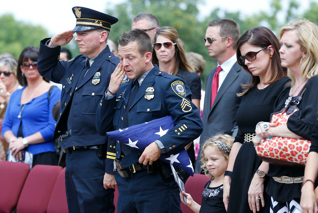 . Oklahoma City police officer Sgt. Ryan Stark, center, wipes a tear from his eye following funeral services for his canine partner, K-9 Kye, in Oklahoma City, Thursday, Aug. 28, 2014. (AP Photo/Sue Ogrocki)