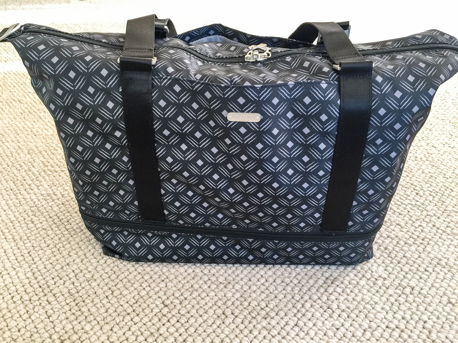 Black and white printed expandable carry on duffle bag packed for a trip.