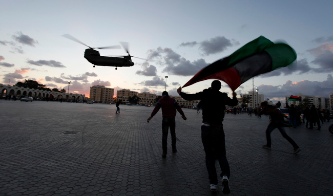 Description of . Libyans run toward a military helicopter, at Nasr Square, during the second anniversary of the uprising that toppled longtime dictator Moammar Gadhafi in Benghazi, Libya, Sunday, Feb, 17, 2013.  (AP Photo/Mohammad Hannon)
