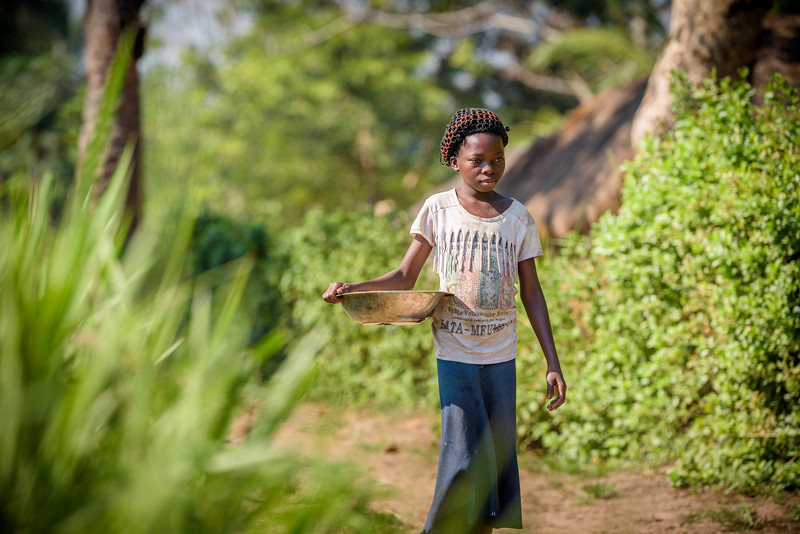 Marie Ngalula, 14 yr-old girl, walks to market, to see her palm nuts. She has to remove the husk by crushing them with rocks. She sells them by the roadside to earn money to buy food for her family. Tubuluku, Kananga, DRC.  Economic Development Marie's father makes and sells charcoal to earn money for the family. He gets about 6,000 Congolese francs p/bag and can do about I per week. It's not enough to support the family so Marie helps by selling palm nuts. Marie sits on the ground next to a pie of palm nuts she's collected. She places one on a rock and pounds it with another rock separating the woody husk from the soft nut inside. When she has enough she'll take them to sell. The buyer will have them mashed and pressed into oil for cooking.  Marie walks the main road in front of the airport with her bowl of nuts. She squats in front of a local market, just across from the main gate.  A woman with a small, green bucket stops. Money changes hands and Marie fill the woman's bucket about halfway. It's all the nuts she has today.  Marie gets 800 francs for the transaction. That's about 50 cents. She needs about a thousand francs to buy enough cassava flour to last the family for two days.   Marie lives with her father, Alexandre Tshimanga, her mother, Ntumba Kalombo Antoinette and her brothers and sisters: 1-Kena Tshimanga, 12 2-Kankonde Moise, 10 3-Munamba Angel, 8 4-Musungayi Andre, 6 5-Mubuyi Tshimanga, 4  Marie lives in a small village outside of Kananga, Democratic Republic of Congo, DRC, called Tubuluku, which means antelopes (plural). Her house is a two-room hut with a thatched roof.  Handful of wooden chairs are the only furniture. She lives here with an extended family of 13.  Home Life Marie is a bright girl but there is a sadness in her eyes. Marie's mother is in the nearby health clinic with a staph infection that has caused a huge abscess on her right side. It has become very serious. As a result, Marie has assumed many of the household duties.  She's force