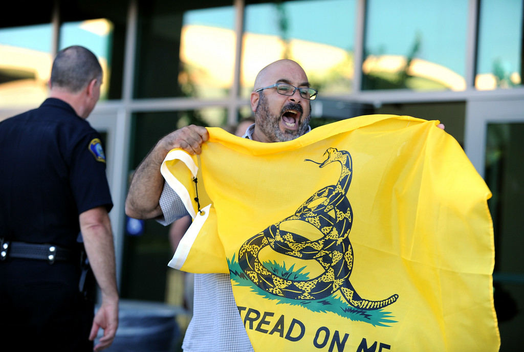. A man yells after being denied taking a flag into a town hall meeting on Wednesday, July 2, 2014 at Murrieta Mesa High School in Murrieta, Ca. The meeting is being held in response to immigrants who were being processed through a Texas Border Patrol Station and delivered to the Murrieta Border Patrol Station on Tuesday, which created protests from both sides of the immigration issue. (Micah Escamilla/The Sun)