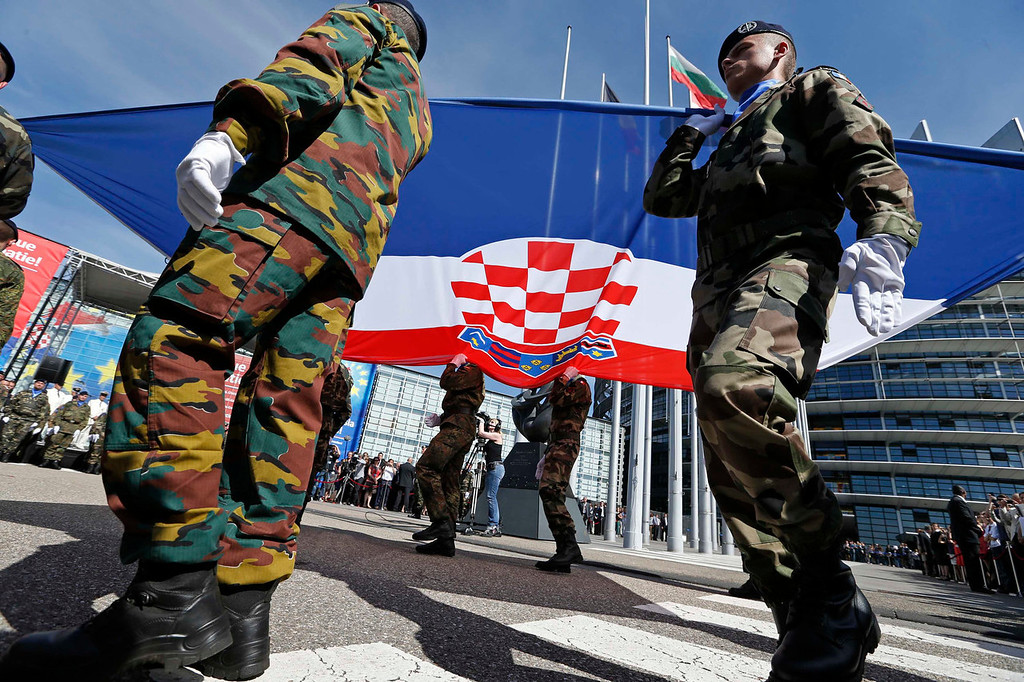 . Soldiers of the Eurocorps hold the flag of Croatia in front of the European Parliament in Strasbourg, July 1, 2013. Two decades since fighting itself free of Yugoslavia, Croatia becomes the 28th member of the European Union on Monday against a backdrop of economic woes in the Adriatic republic and the bloc it is joining. REUTERS/Vincent Kessler