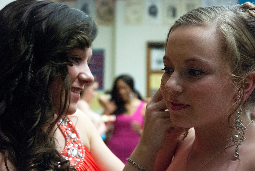 . Kayla Rice/Reformer Katelyn Donovan helps Katie Burroughs with an earring before the evening gown portion of the 2014 Brattleboro Winter Carnival\'s Queen\'s Pageant on Friday night.