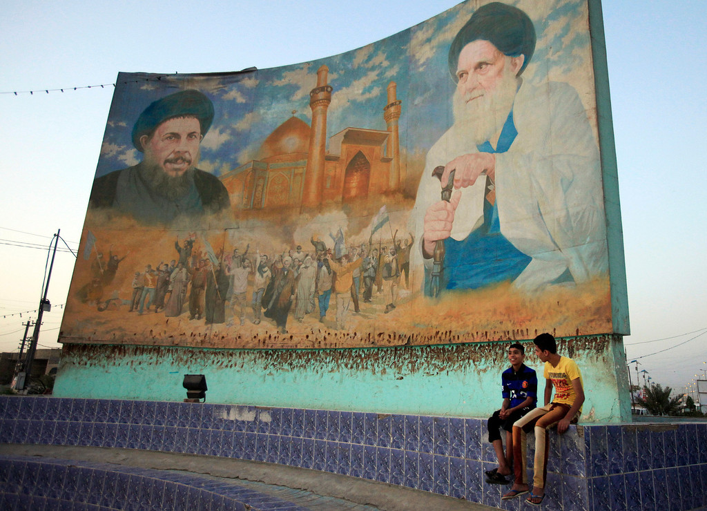 . In this Saturday, April 6, 2013 photo, Iraqi boys sit next to a mural that used to be painted with the portrait of former dictator Saddam Hussein, which turned into a mural of Shiite clerics Ayatollah Mohammed Baqir al-Sadr, left, and Grand Ayatollah Mohammed Sadiq al-Sadr, right, in Baghdad, Iraq. Ten years ago, a statue fell in Paradise Square. Joyful Iraqis helped by a U.S. Army tank retriever pulled down their longtime dictator, cast as 16 feet of bronze. The scene broadcast live worldwide became an icon for a war, a symbol of final victory over Saddam Hussein. But for the people of Baghdad, it was only the beginning. The toppling of the statue on April 9, 2003, remains a potent symbol that has divided Iraqis ever since. (AP Photo/ Karim Kadim)