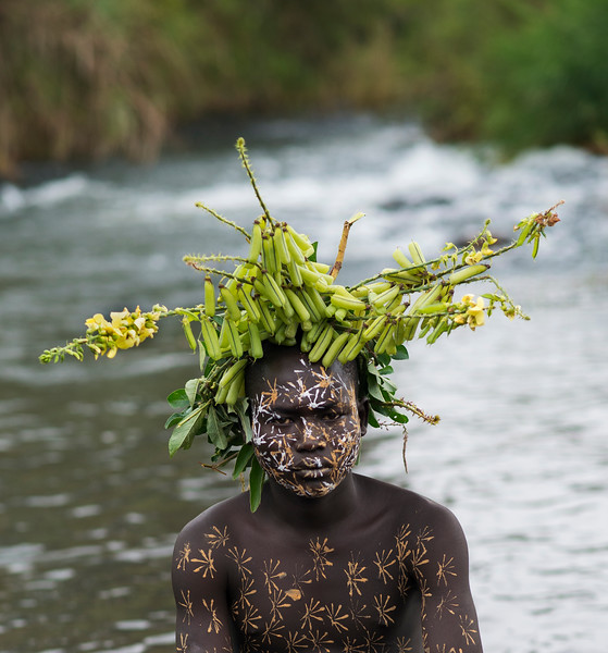 Portrait of a Young Suri boy wearing body paint and natural decorations on the head.  Kibish, Ethiopia, 2017