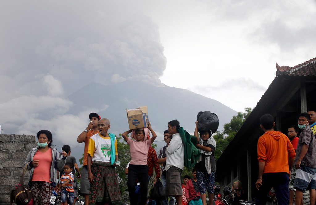 . Villagers carry their belongings during an evacuation following the eruption of Mount Agung, seen in the background, in Karangasem, Indonesia, Sunday, Nov. 26, 2017. The volcano on the Indonesian island of Bali has rumbled into life with a series of eruptions that temporarily disrupted some international flights to the popular tourist destination and dusted nearby resorts and villages with a thin layer of ash. (AP Photo/Firdia Lisnawati