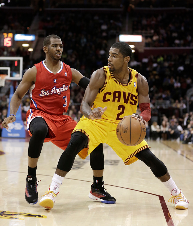 . Cleveland Cavaliers\' Kyrie Irving (2) drives past Los Angeles Clippers\' Chris Paul (3) during the second quarter of an NBA basketball game on Saturday, Dec. 7, 2013, in Cleveland. (AP Photo/Tony Dejak)