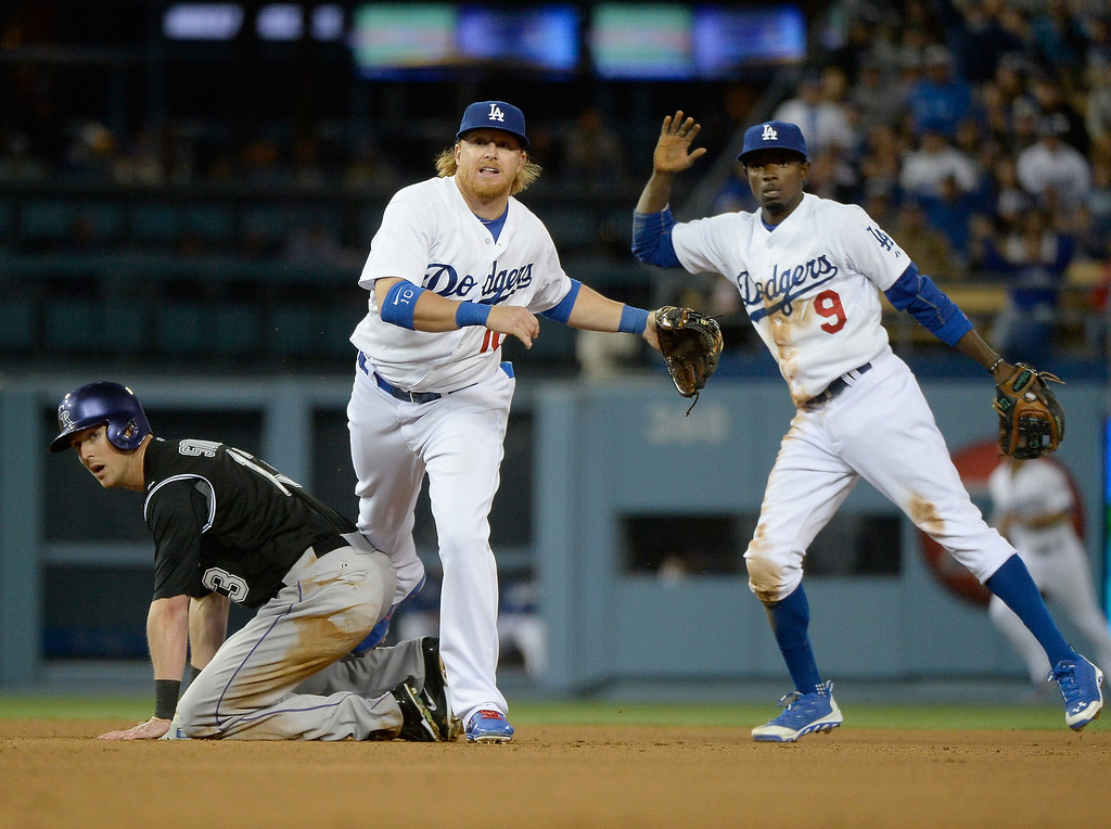 . LOS ANGELES, CA - APRIL 26:  Justin Turner #10 and Dee Gordon #9 of the Los Angeles Dodgers along with Drew Stubbs #13 of the Colorado Rockies react to a double play to end the fifth ining at Dodger Stadium on April 26, 2014 in Los Angeles, California.  (Photo by Harry How/Getty Images)