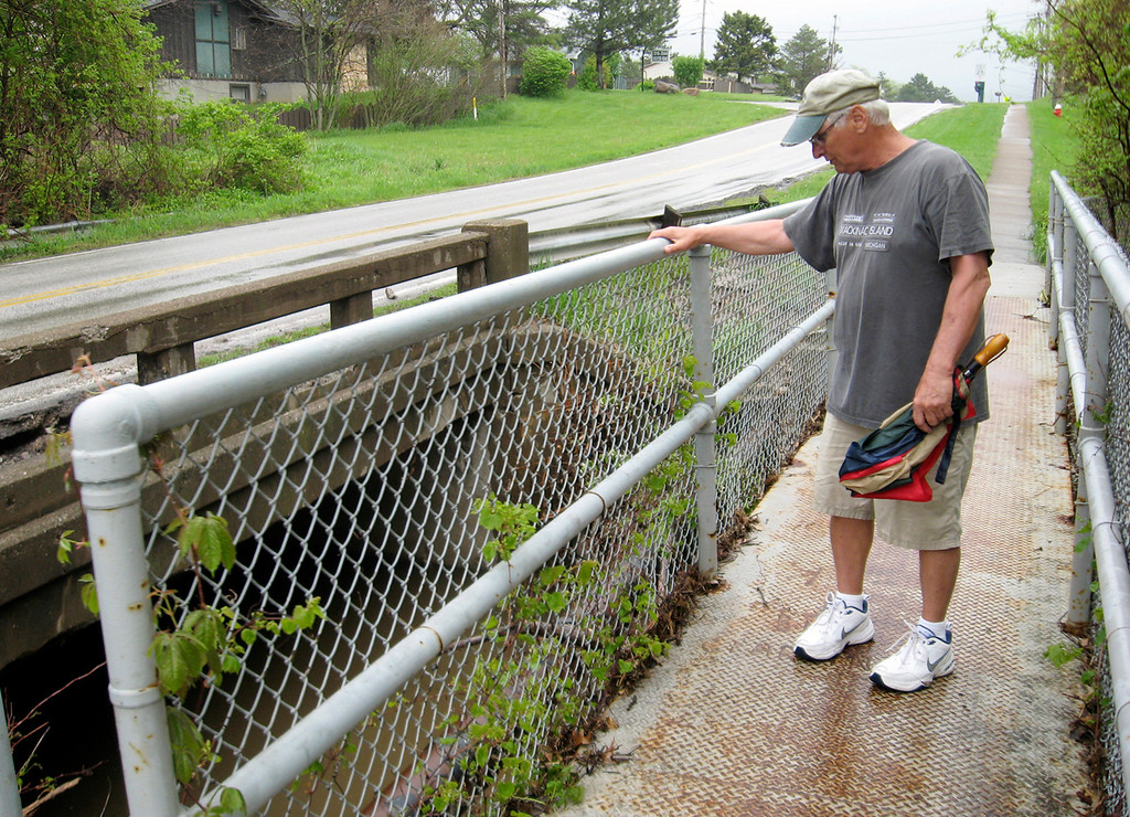 . Rick Payerchin/RPayerchin@MorningJournal.com Lorain resident Cliff Piar stands at the Meister Road bridge over Martin\'s Run in Lorain. Piar said he wants more action from city leaders to clear out the brush and trees that block the flow of water through Martin\'s Run, which relatively small compared to the Black River, but is a key drainage for central and western Lorain.